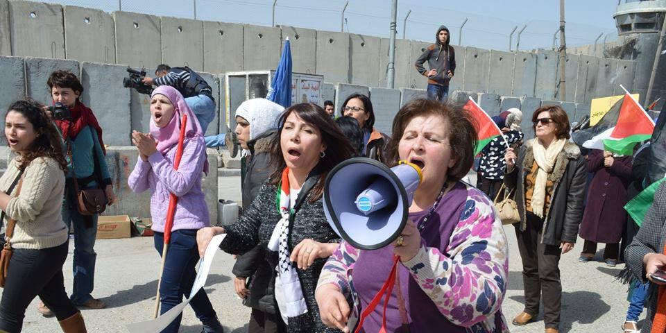 Kvinna till Kvinnas palestinska samarbetsorganisationer demonstrerar under internationella kvinnodagen 8 mars 2015, vid en checkpoint I Ramallah, Västbanken. Foto: PWWSD