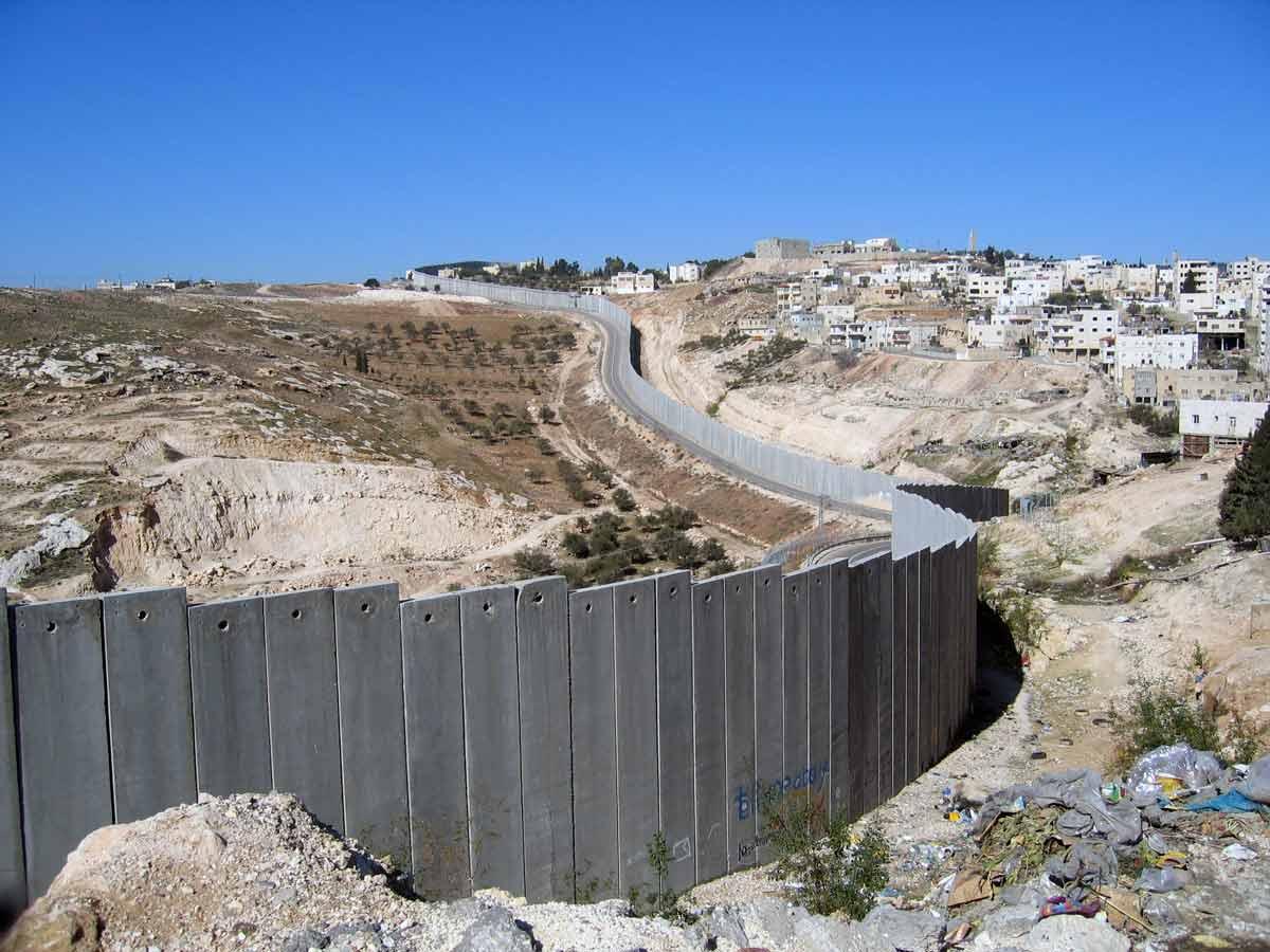 """Israels mur på Västbanken. Som ockupationsmakt har Israel brutit mot internationell humanitär lag i många år när de utför tvångsavhysning av palestinier. I en ny rapport konstaterar Human Rights Watch att vissa """"berövningar är såpass allvarliga att de motsvarar brott mot mänskligheten såsom apartheid och förföljelse""""."""