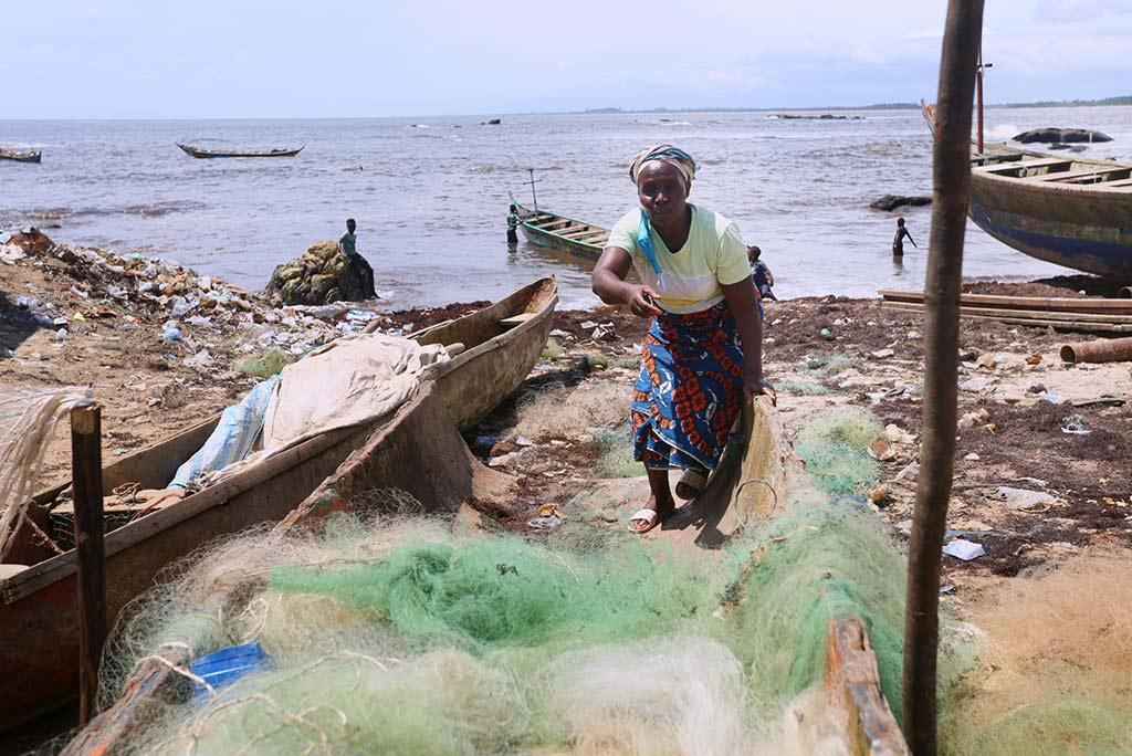 Tupee Nagbo, som är mamma till sju barn, står mitt ibland det som återstår av hennes fiskeverksamhet. Hon gick i konkurs under pandemin, efter 25 år som fiskare. Foto: Wolobah Sali
